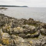Prästens badkar i Vik. Sandstensskikten har böjts ner i stora, runda trattformiga bildningar. Stenshuvud i bakgrunden.